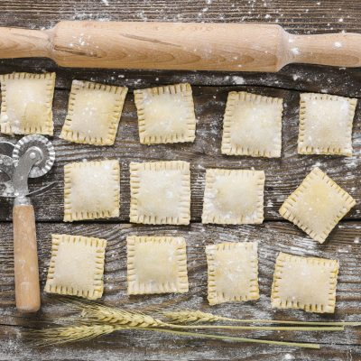 Raw ravioli and tools for their preparation on wooden background
